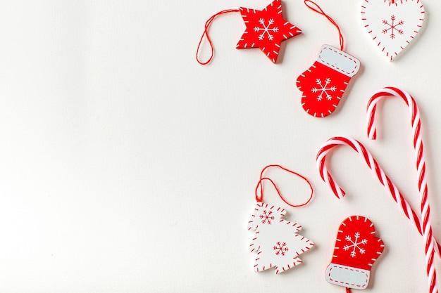 Новогодняя поверхность из конфет и елочных игрушек в бело-красных тонах