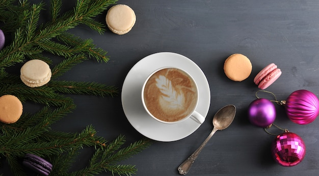 Christmas surface with cup of cappuccino with cake, macarons, christmas toys and tree branches