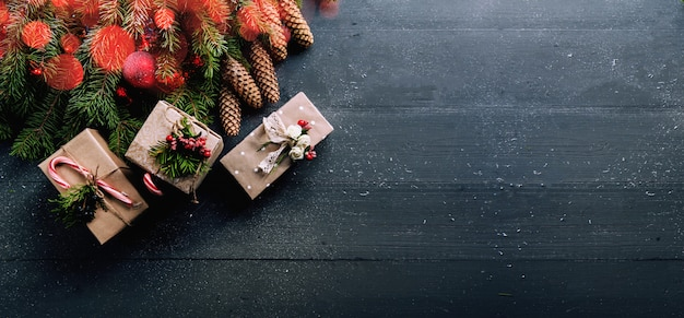 Christmas surface with decorations and gift boxes on wooden board