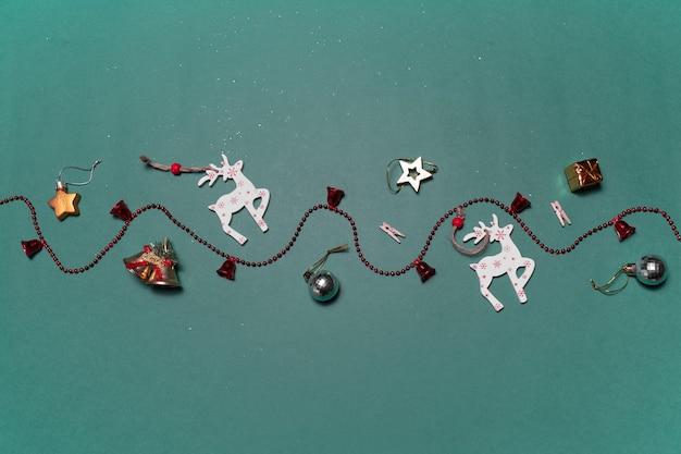 Новогодняя поверхность с декоративными игрушками оленей и подарков на зеленой поверхности