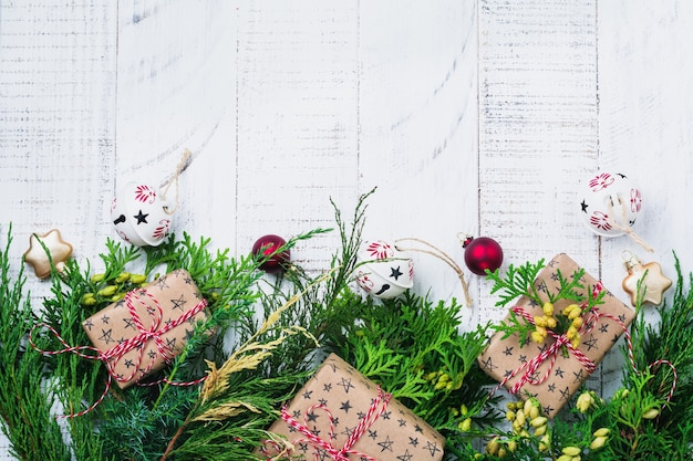 Christmas surface with fir branches, toys, gift box and bells on wooden old surface table