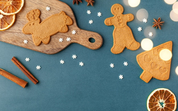 Christmas surface with ginger cookies and spices, christmas lights on a blue surface