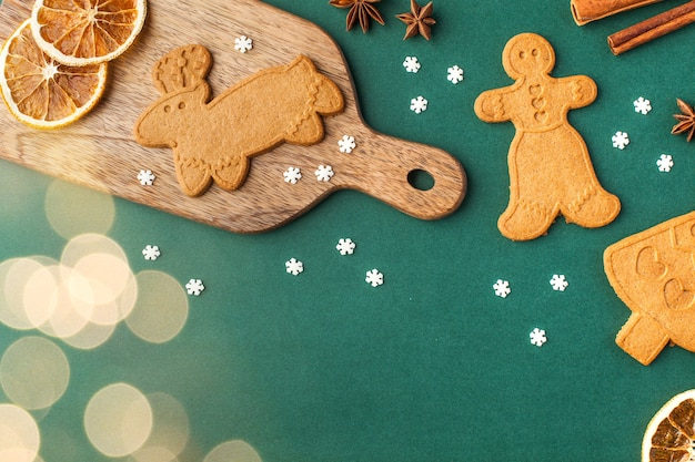 Christmas surface with ginger cookies and spices, christmas lights on a green surface