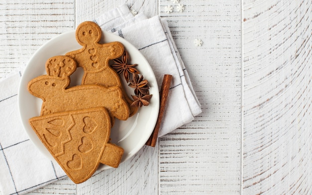 Christmas surface with ginger cookies and spices on a light wooden surface