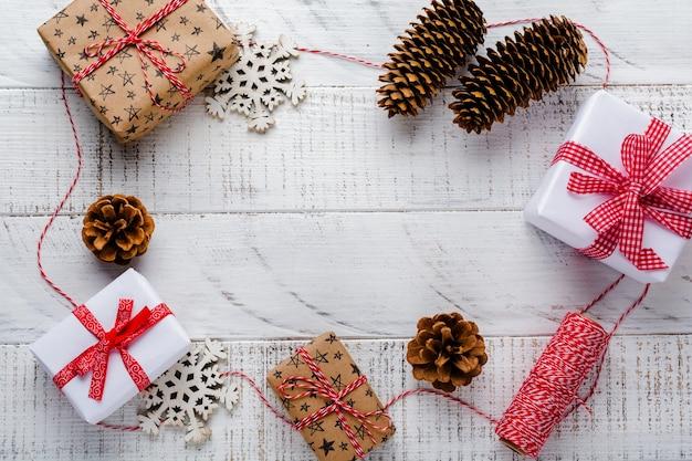 白い木製の古い表面のテーブルに赤いリボン、おもちゃ、ギフトボックス、松ぼっくりのクリスマスの表面。セレクティブフォーカス。