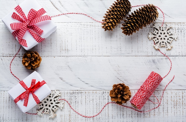 Christmas surface with red ribbon, toys, gift boxes and pine cones on white wooden old surface table. selective focus.