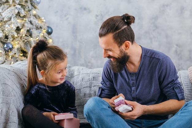 クリスマスのサプライズ。彼女の愛するパパからの贈り物を喜んで受け取るかわいい女の子。