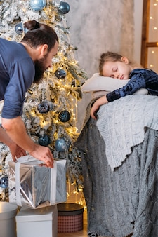 クリスマスのサプライズ。父は、サンタを待っているモミの木のソファで寝ている幼い娘のために、包まれた箱に入った贈り物を受け取りました。