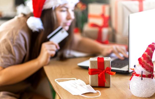 크리스마스 선물 상자 주위에서 인터넷 쇼핑을 하는 노트북을 보고 놀란 여자