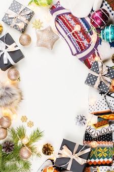 クリスマスセーター、帽子、プレゼント、ライト。冬のコンセプトフラットレイ