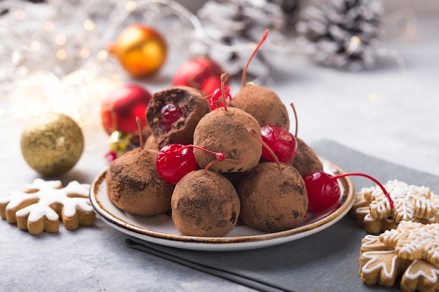 Christmas sweet candies on the dessert table . balls of biscuit with cherry - loli pop or cake pop. new year decoration and apple cider drink. happy holidey concept