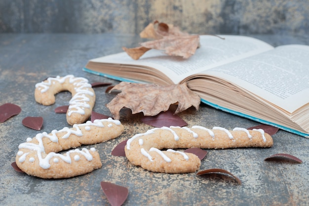 Biscotto dolce di natale con foglia e libro sulla tavola di marmo