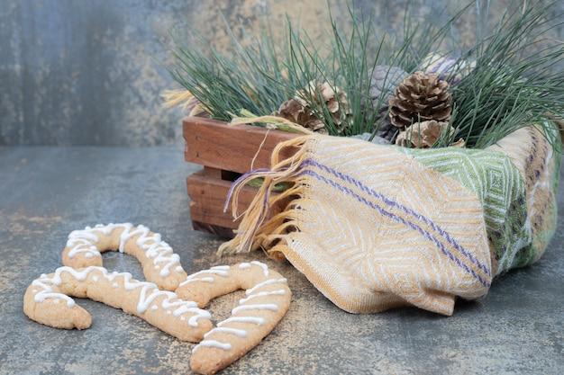 大理石のテーブルのバスケットに松ぼっくりとクリスマスの甘いクッキー
