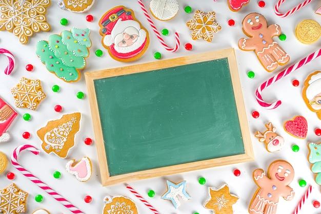 크리스마스 과자 및 칠판. 모듬 축제 크리스마스 과자, 전통 사탕 및 쿠키. 사탕 지팡이 사탕, 진저 브레드, 과자, 간단한 패턴 평면도가있는 flatlay