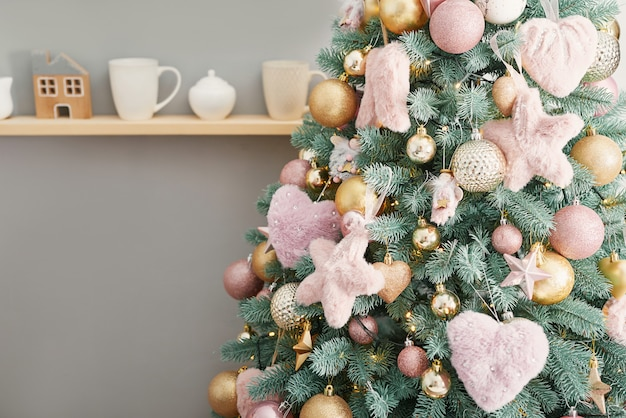 Christmas sweets on background of christmas tree. pink decorated christmas. happy new year!traditional new year dessert. copy space.