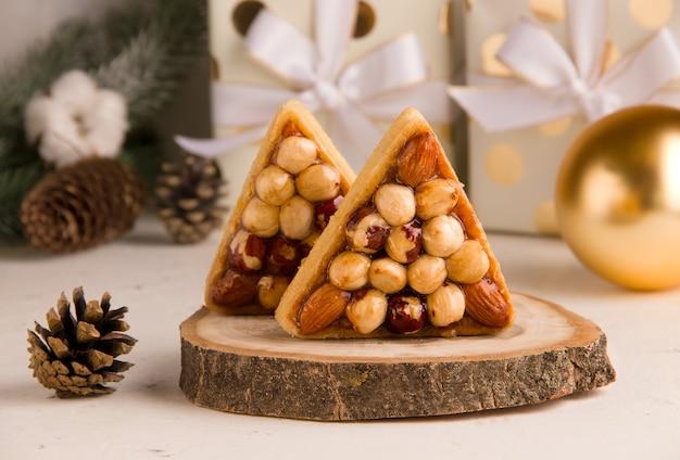 Рождественские сладости на светлом фоне с подарками. печенье с орехами