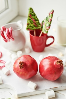 Christmas sweets pomegranate, milk, marshmallows, candies by the window