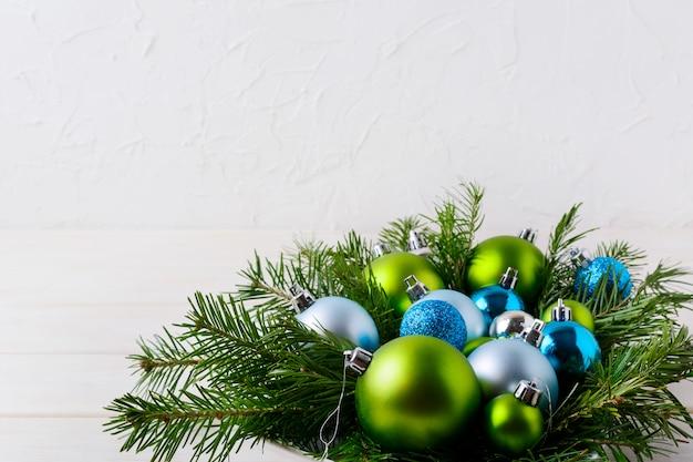 ライトブルー、グリッター、グリーンのオーナメントを備えたクリスマステーブルのセンターピース