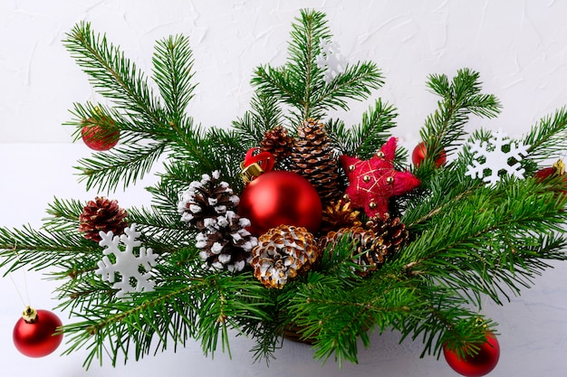Christmas table centerpiece with red balls and hand decorated pine cones