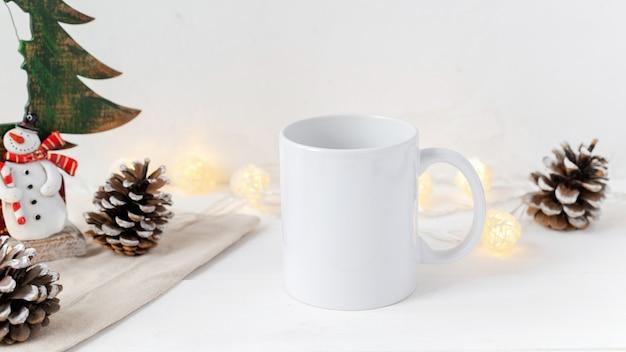 クリスマステーブルの構成。一杯のお茶、モミの実と装飾。白い壁