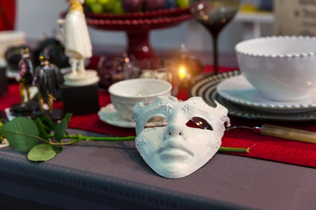 Christmas table decorated with mask, candles and flower closeup, nobody. holiday celebration