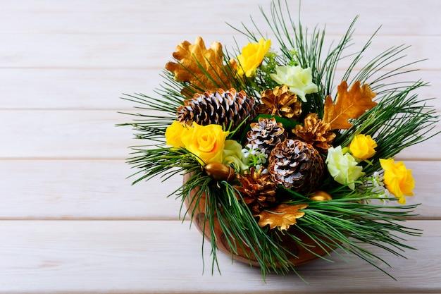 Новогоднее украшение стола с сосновыми ветками и золотыми шишками
