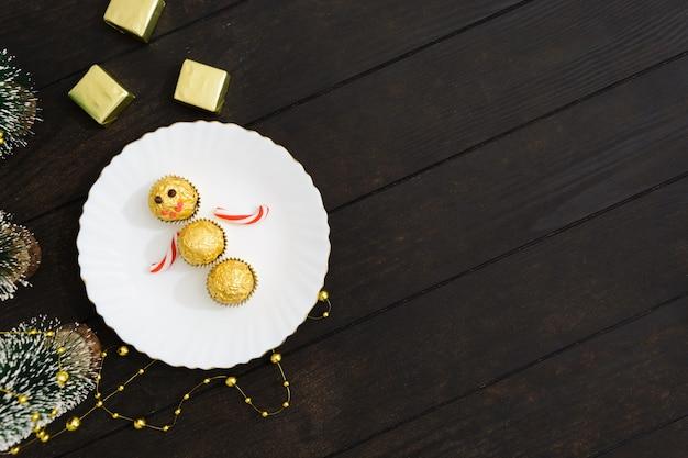 Рождественские украшения стола со снеговиком из конфет на тарелке