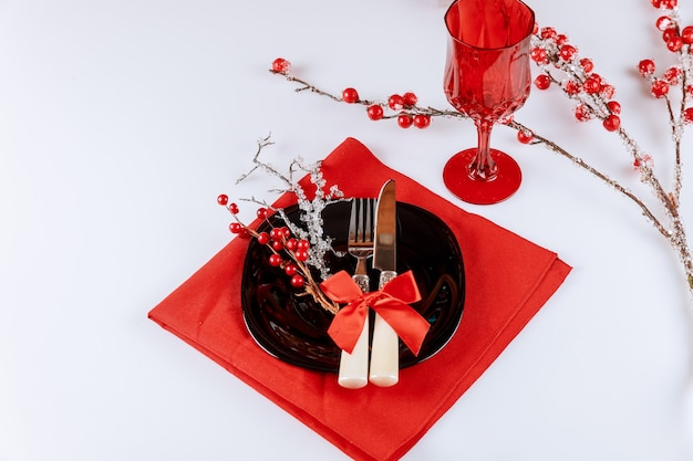 Christmas table dinnerware setting with red berry decorations on white background.