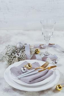 白い背景の上のクリスマステーブルの場所の設定と冬の休日の装飾。季節の休日のコンセプト。