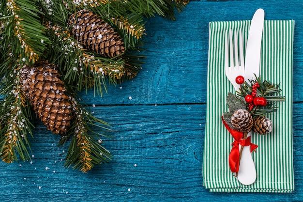 Сервировка рождественского стола - синий стол с зеленой салфеткой, белая вилка и нож, украшенная веточка омелы и рождественские сосновые ветки. рождественские праздники фон.