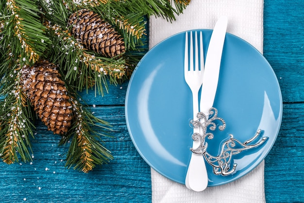 Christmas table place setting - blue table with white napkin, blue plate, white fork and knife, decorated christmas tree toy - silver deer and christmas pine branches. christmas holidays background.