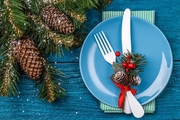 Сервировка рождественского стола украшена веточкой омелы и рождественскими сосновыми ветками. новогодний символ часов. рождественские праздники фон.