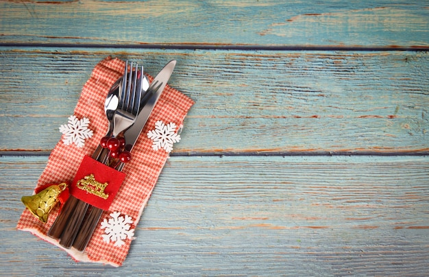 Christmas table place setting decoration with fork spoon and knife on napkin