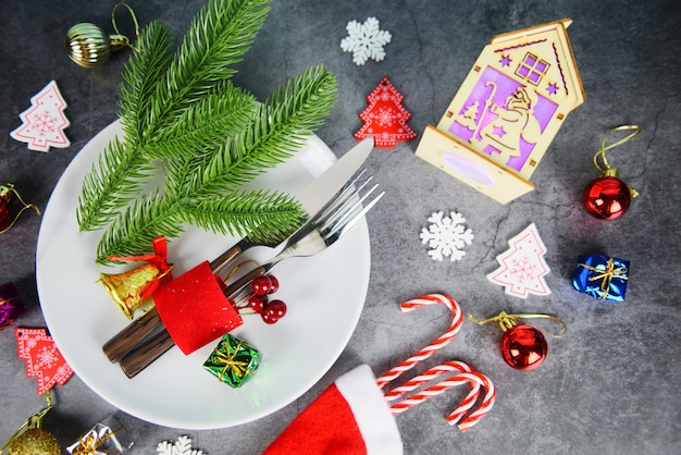 Christmas table place setting decoration with gift box ball candy cane in santa claus hat fork and knife