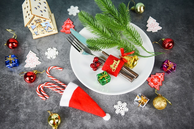 Christmas table place setting decoration with gift box ball candy cane in santa claus hat