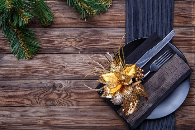 Christmas table place setting with black napkin, plate, fork and knife