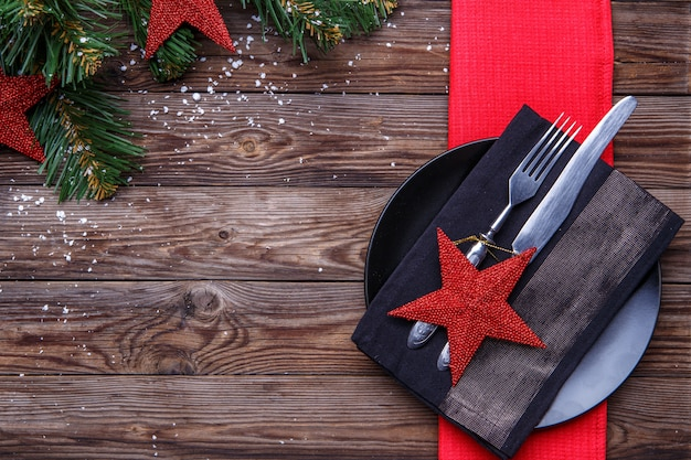 Christmas table place setting with black plate, fork and knife, decorated red star