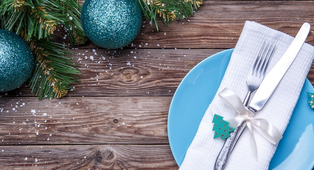 Christmas table place setting with blue plate, fork and knife, decorated ribbon