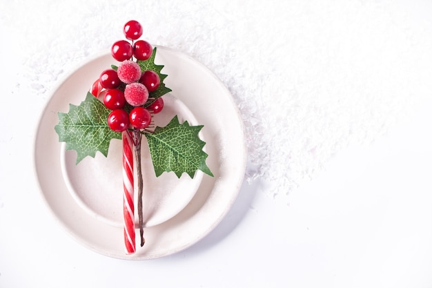 Christmas table place setting with candy cane, berries, holly and white plates. top view. copy space.