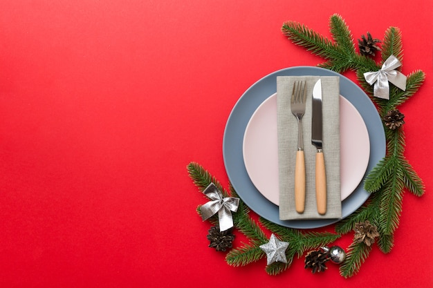 Сервировка рождественского стола с рождественским декором и тарелками, коровами, вилкой и ложкой. рождественский праздник фон. вид сверху с копией пространства