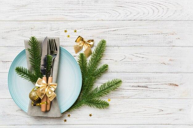 クリスマスの装飾とプレート、キネ、フォーク、スプーンを備えたクリスマステーブルの場所の設定。クリスマス休暇の背景。コピースペースのある上面図