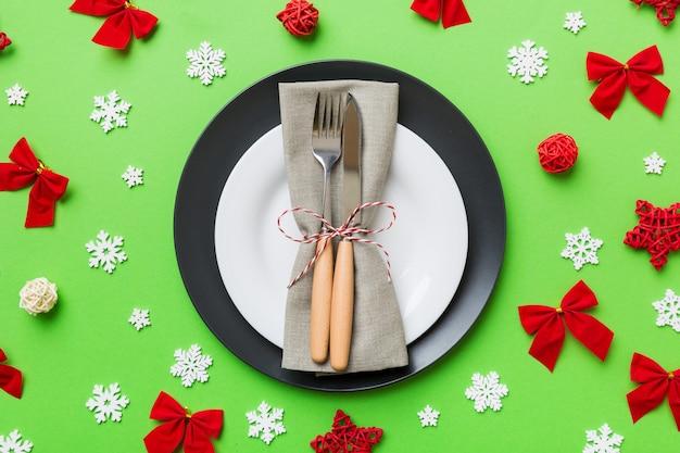 Сервировка рождественского стола с рождественским декором и тарелками, коровами, вилкой и ложкой. рождественский праздник фон. вид сверху