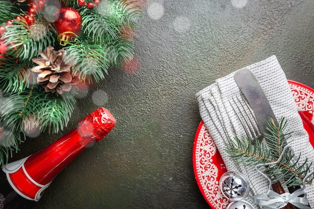 Christmas table place setting with christmas tree branches, champagne, plate, knife and fork over dark table, top view with copyspace. christmas holidays background