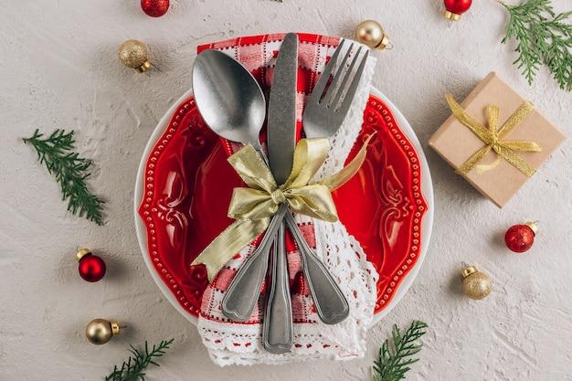 空の赤いプレート、ナプキンのカトラリーとクリスマステーブルの場所の設定