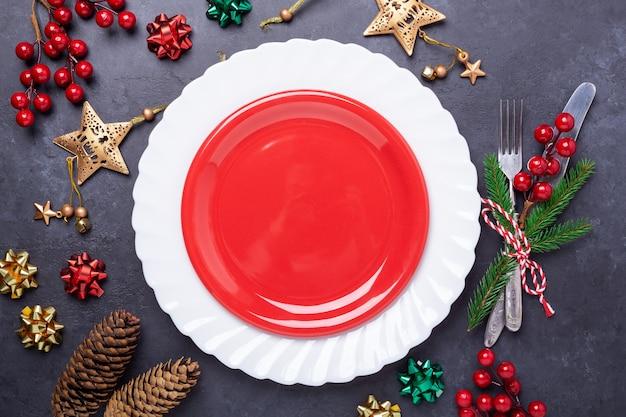 空の赤いプレート、石にお祝いデコレーション星の弓のボールが付いているカトラリーとクリスマステーブルの場所の設定