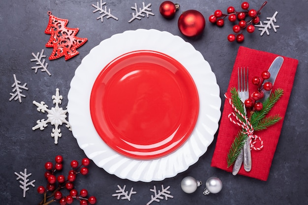 Christmas table place setting with empty red plate, cutlery with festive decorations star bow ball on stone background