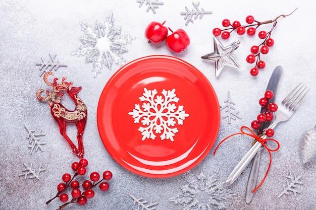 Сервировка рождественского стола с пустой красной тарелкой, столовые приборы с праздничными украшениями