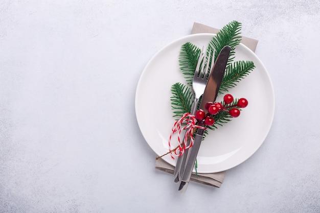 Сервировка рождественского стола с пустой белой тарелкой, леденцами, еловой веткой и столовыми приборами с праздничными украшениями на каменном фоне - изображение