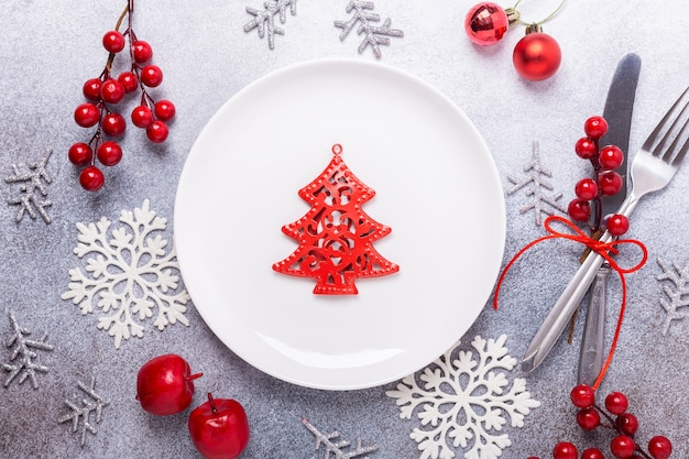 Christmas table place setting with empty white plate, cutlery with festive decorations on stone background
