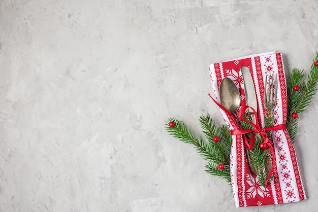 モミの木とコンクリートの背景に装飾が施されたクリスマステーブルの場所の設定。上面図。コピースペースのあるフラットレイ。休日の背景
